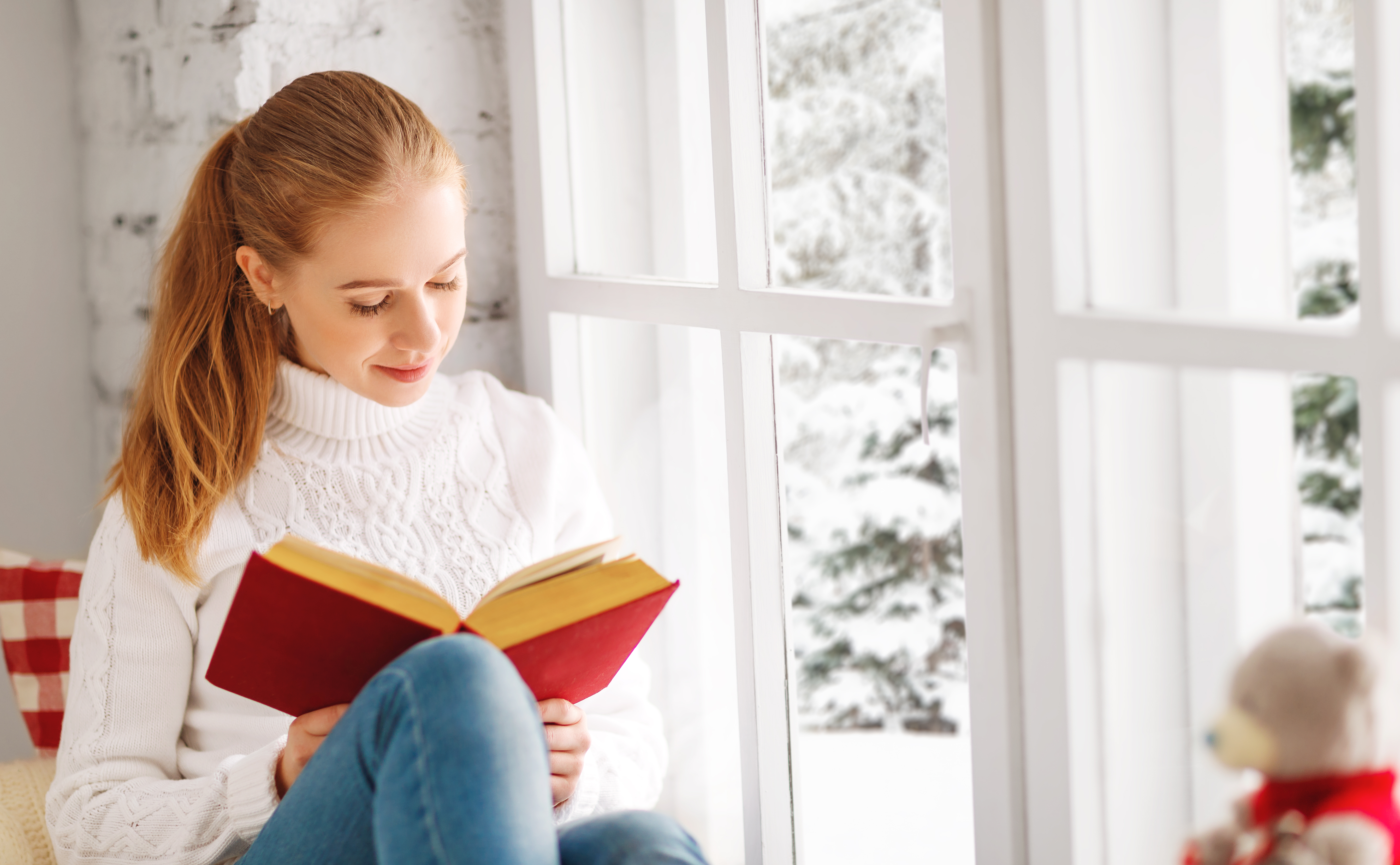 woman reading a book by replacement window in winter